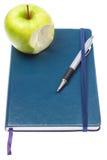 Bitit äpple på anteckningsbokanteckningsboken. royaltyfria bilder