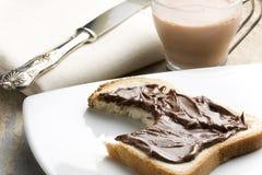 Bitit vitt bröd med Nutella och mjölkar Arkivbild