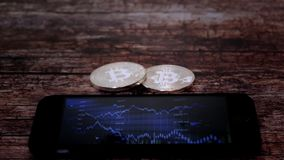 Bitkoyn de dos monedas, mintiendo al lado del smartphone, en la pantalla que exhibe una carta de citas, moneda crypto almacen de video