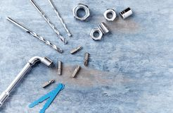Bits for a screwdriver and hex nuts on wooden background. Top view. Copy space royalty free stock photo