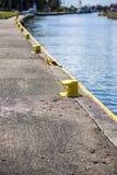 Bitt amarillo en el amarre del muelle del canal del puerto Foto de archivo