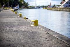 Bitt jaune sur l'amarrage de bord du quai de canal de port Images libres de droits