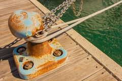 Detail of a bitt with chains and ropes for mooring at the harbor. The bitt is a low cast-iron column in the shape of a mushroom to tie chains and mooring ropes Royalty Free Stock Image
