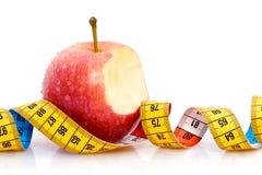 Bitten apple and tape measure stock photos