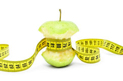 Bitten apple wrapped the measuring tape on a white background Royalty Free Stock Images