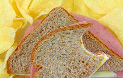 Bitten Bologna And Cheese Sandwich With Chips Stock Image