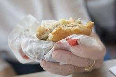 A bitten burger. Woman is holding a bitten burger Stock Images