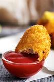Bitten chicken nuggets in small bowl of ketchup Stock Photos