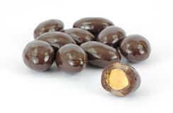 Bitten Chocolate Covered Almond. Chocolate covered almonds with one bitten in the foreground Stock Photos