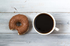 Bitten chocolate donut and cup of black coffee, top view on wooden background Stock Photos