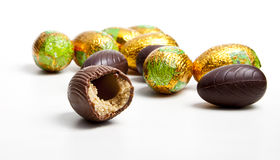 Bitten chocolate egg. And other eggs in foil isolated on white background Royalty Free Stock Photo