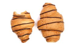 Bitten croissant decorated with chocolate sauce isolated on white background, top view.  stock image