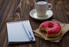 Bitten donut cup of coffee and notebook. Selective focus royalty free stock images