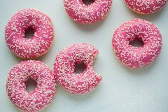 Bitten donut. Sweet icing sugar food. Dessert colorful snack. Glazed sprinkles. Treat from delicious pastry breakfast. Bakery cake royalty free stock images