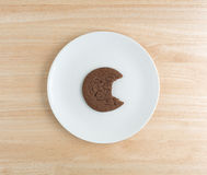 Bitten Dutch cocoa cookie on a white plate Royalty Free Stock Photography