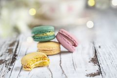 Bitten French Macaron. Bite missing from a lemon french macaron in front of a stack of macarons on a white rustic table stock image