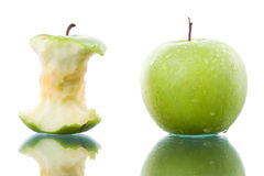 Bitten and fresh green apple. Fresh and bitten green apple side by side on glass table Stock Photography