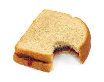 Bitten grape jelly sandwich. A grape jelly sandwich on wheat bread that has been bitten on a white background royalty free stock images