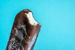 Bitten ice cream lolly in chocolate glaze close-up with condensate and icing frost. On a blue background stock photos