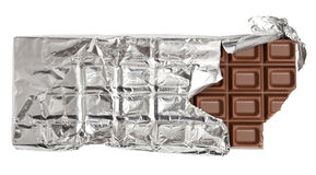 Bitten milk chocolate bar. In tinfoil stock photos