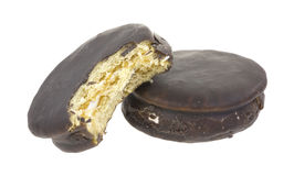 Bitten moon pie. A bitten moon pie against a full size chocolate pie on a white background stock images