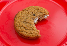 Bitten oatmeal crème cookie on a red plate Royalty Free Stock Images