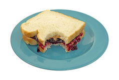 Bitten peanut butter jelly sandwich. A peanut butter and jelly sandwich that has had one bite on a blue plate against a white background royalty free stock photography