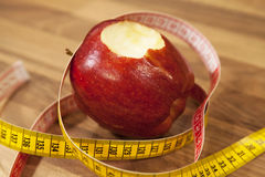 Bitten red apple and tape measure. Royalty Free Stock Images