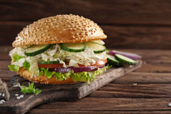 Bitten veggie burger on a wooden board Royalty Free Stock Photos