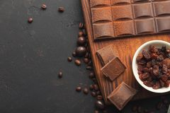 Crushed chocolate pieces and raisons on gray background stock photo