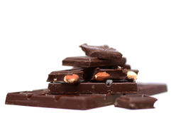 Bitter chocolate with nuts. Tiles and bits of dark chocolate with almonds on white background Royalty Free Stock Photos
