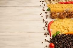 Bitter glödhet peppar med olika sorter av pasta på en vit träbakgrund Arkivfoto