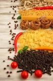 Bitter glödhet peppar med olika sorter av pasta på en vit träbakgrund Royaltyfri Bild