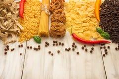 Bitter glödhet peppar med olika sorter av pasta på en vit träbakgrund Arkivfoton