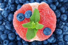 A bitter grapefruit, sweet blueberries and fresh mint as a background. Nutritious citrus in a center of bilberries. Royalty Free Stock Image