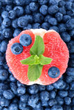 A bitter grapefruit, sweet blueberries and fresh mint as a background. Nutritious citrus in a center of bilberries. Royalty Free Stock Photo