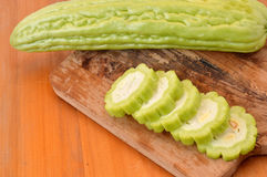 Bitter melon. On board chopped at wooden table Stock Photography