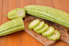 Bitter melon. On board chopped at wooden table Stock Photos