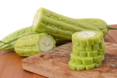 Bitter melon. On board chopped at wooden table Stock Photo