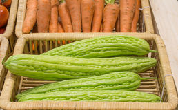 Bitter melon  and carrots harvested products on wooden basket. Royalty Free Stock Photos