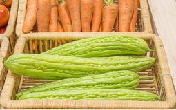 Bitter melon  and carrots harvested products on wooden basket Stock Photography