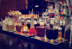 Bitters and infusions on bar counter, toned. Bitters and infusions on bar counter, bar bottles in blurred background, toned image Royalty Free Stock Photos