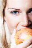 bitting苹果的妇女的特写镜头画象 免版税库存图片