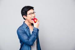 bitting红色苹果的年轻亚裔人 免版税库存照片