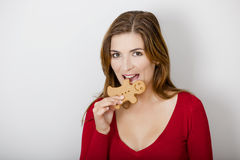 Bitting a Gingerbread cookie. Beautiful young woman bitting a gingerbread cookie royalty free stock image