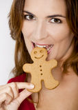Bitting a Gingerbread cookie. Close-up portrait of a beautiful young woman biting a gingerbread cookie royalty free stock photos