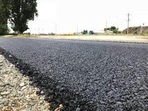Bitumen Asphalt Road. Fresh bitumen asphalt road. Quality cover asphalt. Road construction company make a asphalted road stock photo
