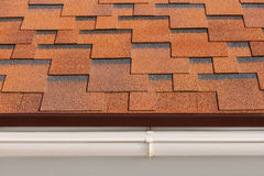 Bitumen asphalt shingles. Bitumen asphalt shingles with plastic drainage on house roof Stock Photography