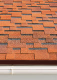 Bitumen asphalt shingles. Bitumen asphalt shingles with plastic drainage on house roof Royalty Free Stock Image