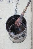 Bitumen-Emulsion im Blecheimer, der mit einem Besen angewendet wird lizenzfreies stockfoto